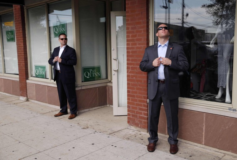 """Secret Service agents keep watch as U.S. President Barack Obama visits a Pat Quinn campaign office in Chicago in this October 20, 2014 file photo. Two agents were posted outside this generic campaign office, and the simplicity of the setting and placement of the agents caught my eye. I took about 10 frames, and then one agent looked up. The juxtaposition of the agents was visually interesting and unique to me. For White House news photographers, a lot of what we do is orchestrated in advance. """"Different"""" images can be few and far between.†To capture a photo that is not preconceived or influenced by the political image makers is quite satisfying. Taking these photos is one of the greatest challenges in this kind of work. At the end of the day, the job of a Secret Service Presidential Protective Detail agent and a White House press travel pool photographer are not all that different. We go everywhere the President goes, we are ready to react to anything that might happen to the President, we think on our feet, we spend lots of hours waiting, we spend a lot of time on the road, we work strange hours and we are very close with our colleagues. Of course there some major differences.† While we watch the President the agents scan the crowd. We carry cameras and they carry guns. Oh, they also tend to look a whole lot sharper than we do....those suits, haircuts and sunglasses do not come cheap. - Kevin Lamarque"""