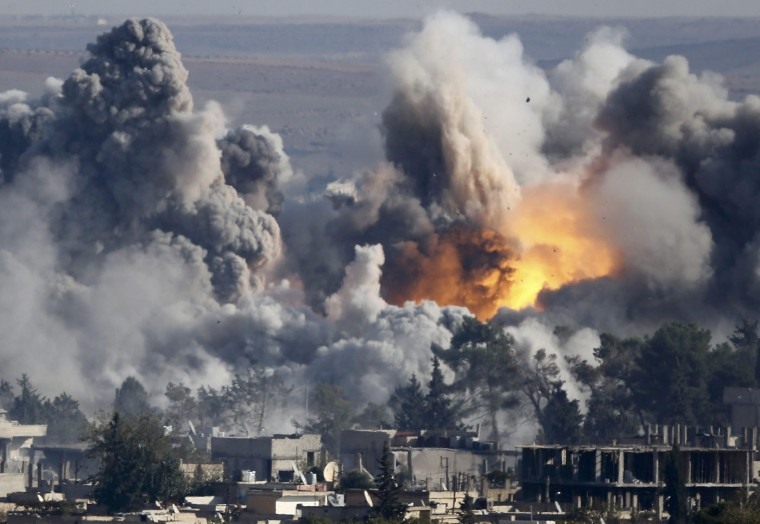 """Smoke rises over Syrian town of Kobani after an airstrike, as seen from the Mursitpinar border crossing on the Turkish-Syrian border in the town of Suruc in this file October 18, 2014 file photo. A U.S.-led military coalition has been bombing Islamic State fighters who hold a large swathe of territory in both Iraq and Syria, two countries involved in complex multi-sided civil wars in which nearly every country in the Middle East has a stake. The Turkish military and police had declared the Turkish-Syrian border area a """"military zone"""", which limits the ability of the press to move around. In these days of modern warfare, the weaponry is more powerful than that in the old days. So all of my colleagues and I have to be doubly careful to ensure we do not end up in the line of fire, as positions of Kurdish YPG fighters and IS militants change quickly. For all those reasons, to stay away is the only solution at the moment. We ended up on hills about 2km (1.24 miles) away from Kobani using very long telephoto lenses, often more than 1000mm, to get a peek into the city while listening to the sound of war and smelling its scent. Sometimes you see a shadow of a fighter hiding behind a building and more often you see the massive impact of heavy airstrikes. It is a bit strange sitting there with lenses I usually use for sports photography alongside people from the area, who come to the hills to see what's going on. They bring binoculars and make tea - making it almost seems like a tourist attraction. - Kai Pfaffenbach"""