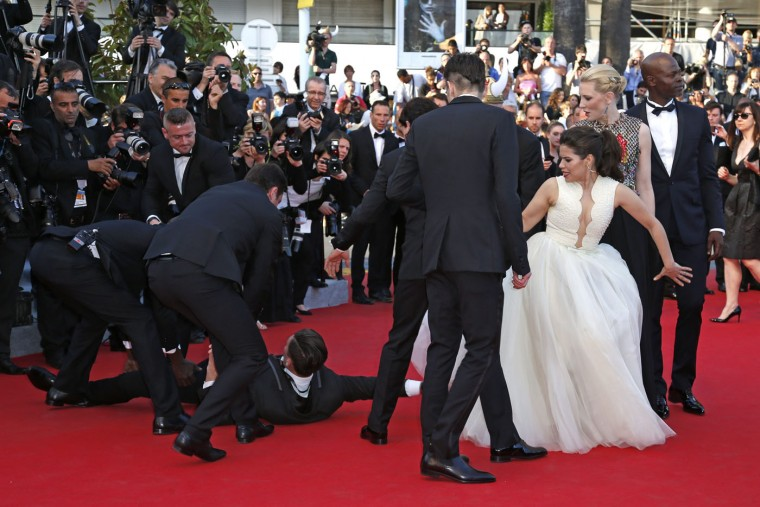 """A man is arrested by security as he tries to slip under the dress of actress America Ferrera (3rd R) in Cannes in this May 16, 2014 file photo. I was covering the stars' red-carpet arrival for the film screening of """"How to Train Your Dragon 2"""". Suddenly Vitalii Sediuk, a Ukrainian journalist also known as a red-carpet prankster, tried to stick his head under actress America Ferrera's netted skirt. No doubt feeling fabulous in her beautiful couture gown, the moment was clearly ruined for Ferrera. I had only ten seconds to realise what was happening and take the shot. Security rapidly dealt with the culprit amid shocked looks from Ferrera and co-star Cate Blanchett. After a flash of appearing red faced and confused, the actress continued the red carpet walk as if nothing had happened. - Benoit Tessier"""