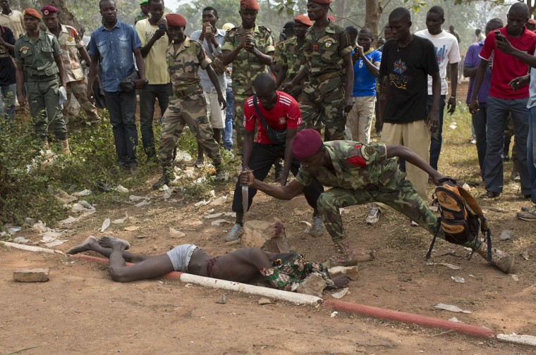 Central African Army (FACA) soldier stabs the corpse of a man, who was killed as he was accused of joining the ousted Seleka fighters, in the capital Bangui in this February 5, 2014 file photo. I was heading back to the hotel to file after a ceremony in Bangui, where the interim president had promised to reinstate the country's armed forces, urging for national unity. I was in the taxi for just a few minutes when my fixer asked me to come back as people were attacking and killing a man. The crowd was in a violent, bloodthirsty frenzy and I tried to stay alert; an angry crowd can be dangerous, unpredictable and very scary, something I had unfortunately witnessed there before. The lifeless body of the victim, suspected of having joined the former Seleka rebel group, was being dragged, kicked, stabbed and pelted with rocks by Central African Republic soldiers. Although no one noticed the journalists, I didn't feel like witnessing the lynching for a moment longer than I thought necessary. I must have stayed at the scene for no more than ten minutes. I don't believe that photographers should ever get used to witnessing such violence and the event definitely affected me. Still, during these situations, I try to protect myself by not allowing certain memories to linger in my mind too long. I believe this picture is a strong reminder of how deep the thirst of revenge runs in the country and how difficult it will be for any internal or external force to stabilise and bring long lasting peace in the Central African Republic. - Seigfried Modola