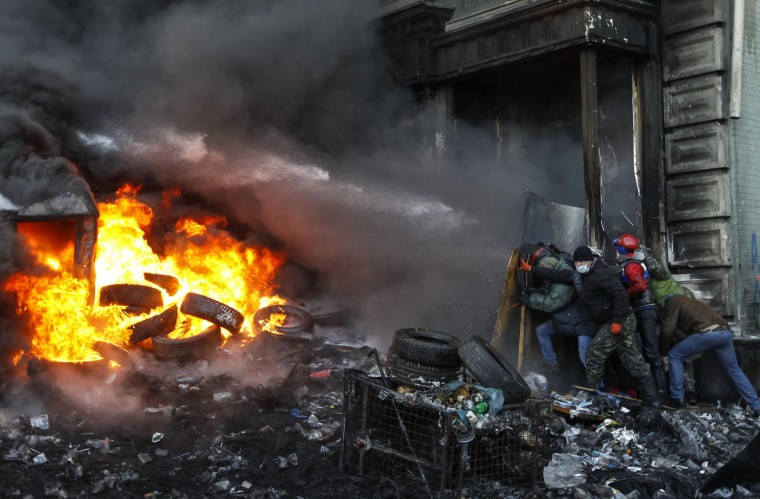 Pro-European integration protesters take cover from water sprayed from a fire engine at the site of clashes with riot police in Kiev in this January 23, 2014 file photo. Everyday protestors moved up to the barricades, made from burnt buses and cars, to clash with the police. It was winter, cold, and police used water hoses to turn the streets in front of the barricades to ice. The protestors kept moving up to the police positions to throw molotov cocktails and the police kept driving them back with rubber bullets and water hoses. This was happening for many days. Molotov cocktails were everywhere - in the air, being thrown at the police and behind barricades ready to be used. The flag of Ukraine was seen everywhere, and one song was sang many times a day - the Ukraine anthem. To shoot pictures every day in a bulletproof vest and helmet, while walking among the piles of burnt tires and avoiding rubber bullets was a challenge. I was surprised by the strong desire of the protestors to change something in their life, how they helped each other - many people, including the very old, brought warm clothes and hot food to them. - Vasily Fedosenko