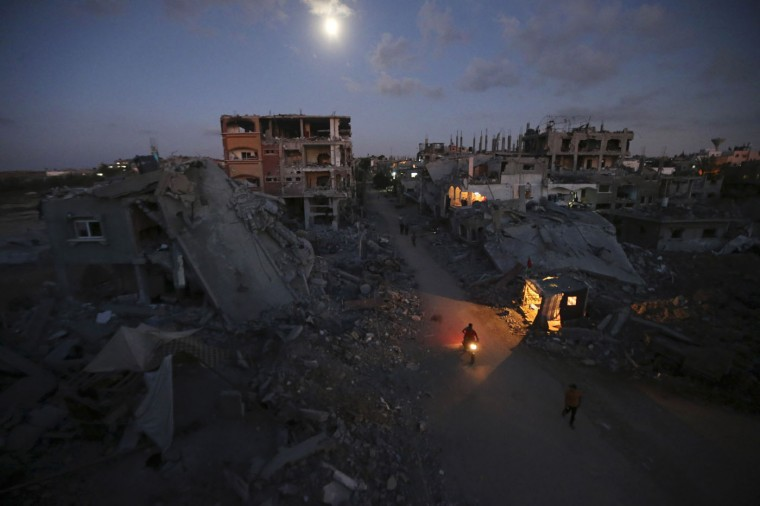 Palestinian pedestrians and a motorcyclist commute along a road between ruins of houses, which witnesses said were damaged or destroyed during the Israeli offensive, in Beit Hanoun town in the northern Gaza Strip in this September 7, 2014 file photo. I was shooting pictures of houses that were destroyed during the 51-day war in Gaza to cover the life of displaced people after the offensive. I was moving from the ruins of one house to another adjacent house where people were staying in makeshift shelters in their devastated neighbourhood. The man riding a motorcycle past destroyed houses captured my attention. It was not easy to get the picture as the light was very dim and I was very lucky that a light from a car illuminated the motorcycle. - Mohammed Salem