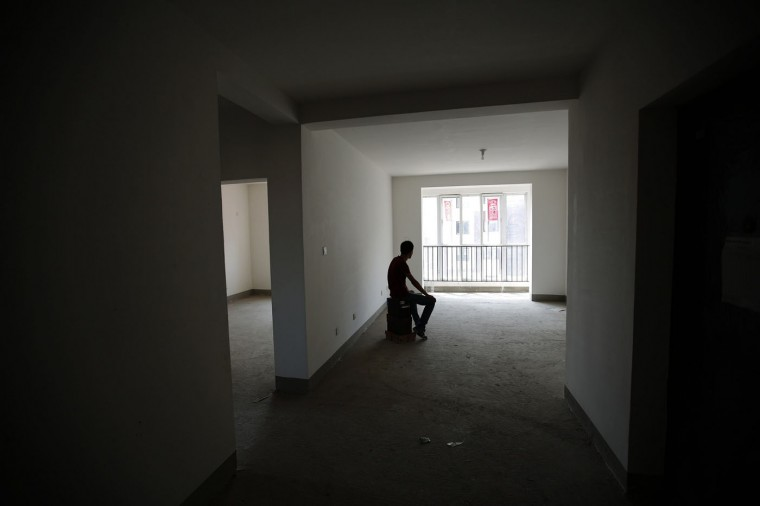 Zhiliang, whose fiancee was onboard Malaysia Airlines Flight MH370 which disappeared on March 8, 2014, is silhouetted at an empty house which he had planned to decorate with her for their marriage, in Tianjin, in this August 26, 2014 file photo. Almost six months had passed since the Malaysian Airlines MH370 disappeared. Although authorities concluded that the plane crashed in the remote Indian Ocean and lost all the passengers, many family members refuse to accept that conclusion. They hope that they are still alive. However, public interest towards this incident faded, so I decided to record what these family members are still going through and shed light on this mysterious incident once again. I thought that portrait-style pictures showing family members together with the missing passengers' mementos would tell a story. I was very careful not to hurt their feelings or invade their privacy when taking these pictures. My first priority was showing my respect for the family members, so before photographing them, I would wait to ask their permission to take pictures until I felt that they were ready and would always spend some time listening to them talk. Sometimes this brought tears to my eyes. - Kim Kyung Hoon