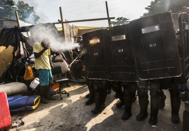 Riot police use pepper gas against residents of the Telerj slum as they attempt to repossess the land in Rio de Janeiro, in this April 11, 2014 file picture. I was shooting the clear-out by the police of a building which belonged to a giant telecommunications company and had been taken over by homeless people a week earlier. It was my third day there as I was doing a photo essay on the occupation and I was more interested in the aesthetics of the shacks and how people managed to build a home. Still, there was tension in the air that the police could invade the place at any moment. When I arrived that morning, it was still dark and I saw more than 1,000 police officers surrounding the area. Some of the homeless were leaving on their own but there was a lot of confusion and small riots outside. I took this picture about 15 minutes after I managed to enter the area, which was very challenging. The image is both strong and sad because the man is poor, black, unarmed and helpless against a whole squad of a heavily armed police spraying tear gas right into his eyes. - Ana Carolina Fernandez