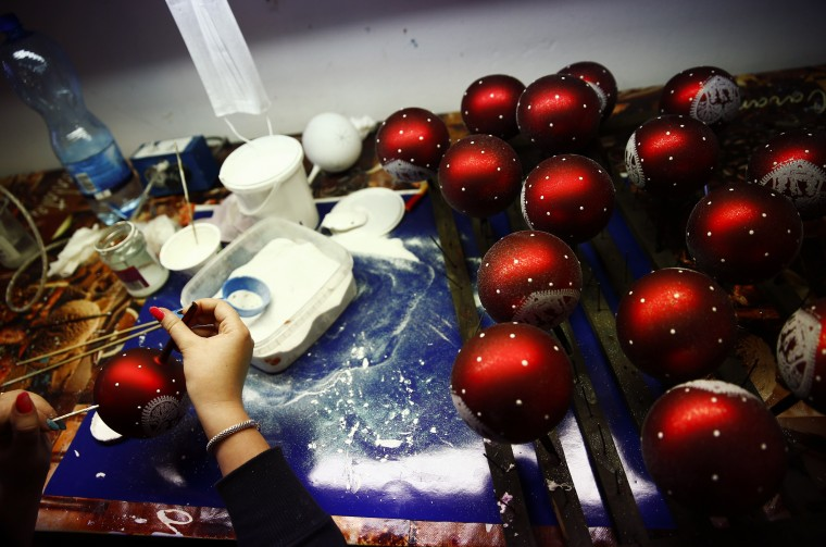 A worker paints Christmas decorations on glass baubles at the Silverado manufacture of hand-blown Christmas ornaments in the town of Jozefow outside Warsaw December 2, 2014. REUTERS/Kacper Pempel