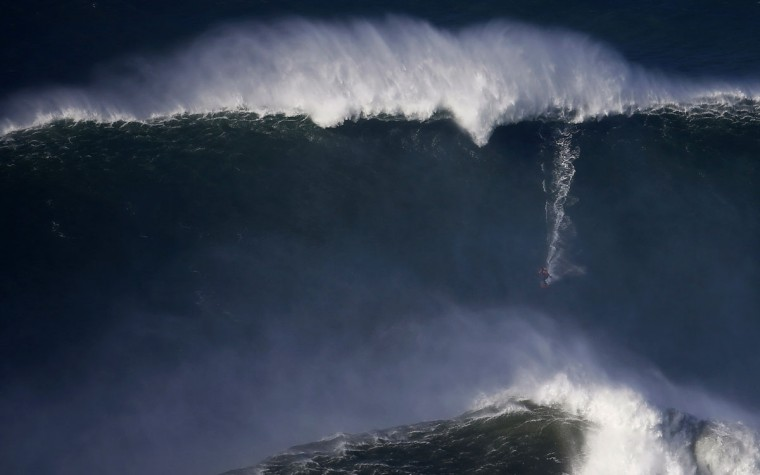 A surfer drops in on a large wave at Praia do Norte, in Nazare December 11, 2014. Praia do Norte beach has gained popularity with big wave surfers since Hawaiian surfer Garrett McNamara broke a world record for the largest wave surfed here in 2011. (Rafael Marchante/Reuters)