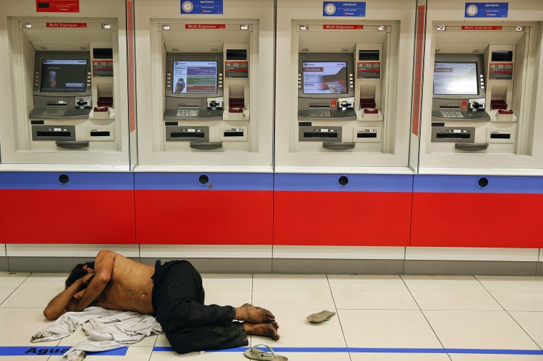 A man sleeps in front of ATM machines on Paulista Avenue in central Sao Paulo, in this June 8, 2014 file photo. REUTERS/Damir Sagolj