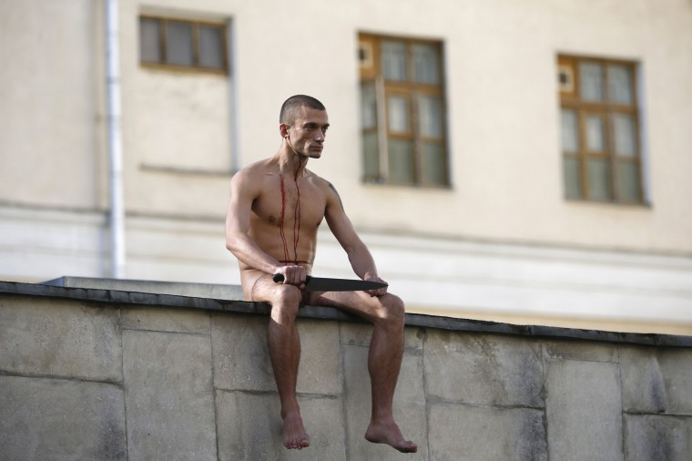 """Artist Pyotr Pavlensky sits on the wall enclosing the Serbsky State Scientific Center for Social and Forensic Psychiatry after he cut off a part of his earlobe during his protest action titled """"Segregation"""" in Moscow, in this October 19, 2014 file photo. REUTERS/Maxim Zmeyev/Files"""
