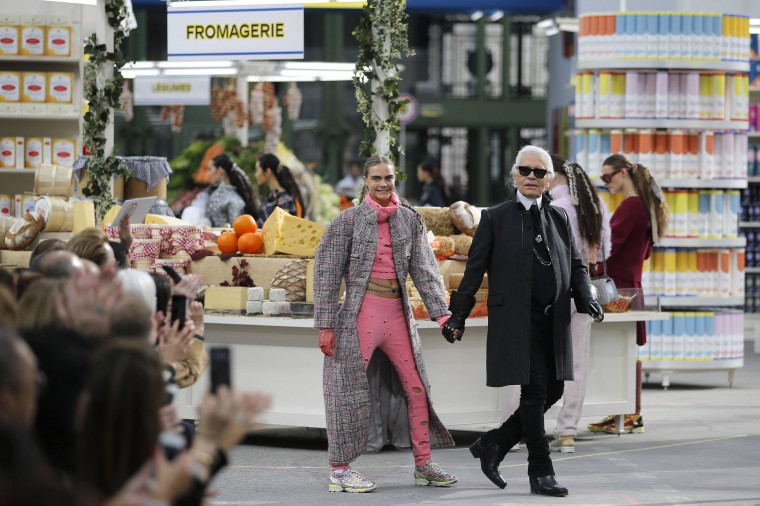 """German designer Karl Lagerfeld (R) and British model Cara Delevingne appear at the end of his Fall/Winter 2014-2015 women's ready-to-wear collection show for French fashion house Chanel at the Grand Palais transformed into a """"Chanel Shopping Center"""" during Paris Fashion Week, in this March 4, 2014 file photo. REUTERS/Stephane Mahe/Files"""