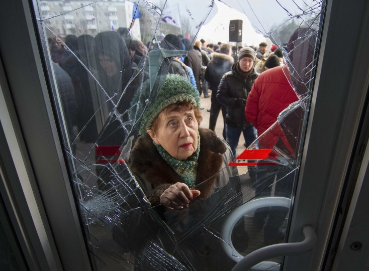A woman looks through a damaged door as pro-Russian demonstrators hold a rally outside the regional government building in Donetsk, in this March 3, 2014 file photo. REUTERS/Stringer/Files