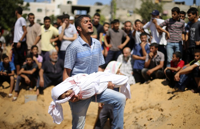 A Palestinian man reacts as he carries the body of a girl from the Abu Nejim family, whom medics said was killed along with other eight family members by an Israeli air strike, before her burial at a cemetery in Beit Lahiya in the northern Gaza Strip, in this August 4, 2014 file photo. REUTERS/Mohammed Salem
