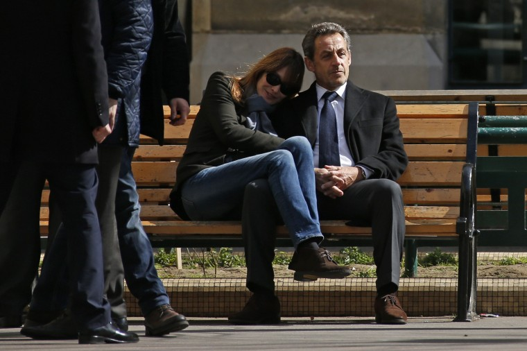 Former French president Nicolas Sarkozy (R) sits on a bench with his wife, singer Carla Bruni-Sarkozy, after voting at a polling station in the first round in the French mayoral elections in Paris, in this March 23, 2014 file photo. REUTERS/Benoit Tessier