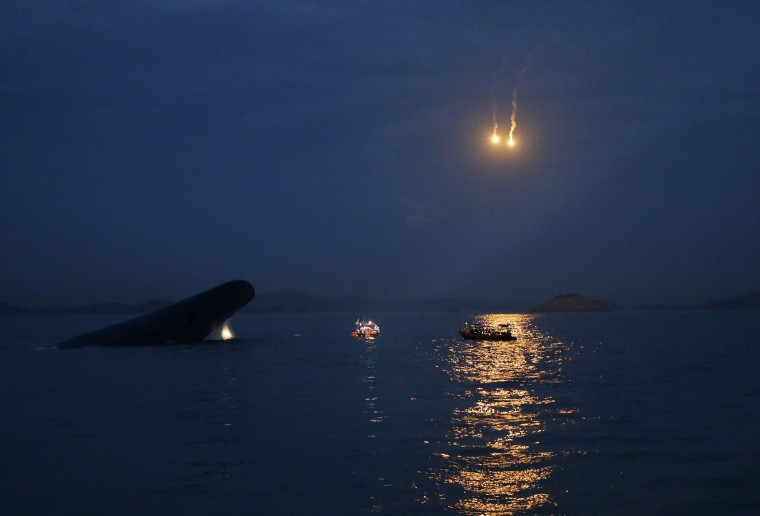 The South Korean Sewol ferry (L) is seen sinking in the sea off Jindo, as lighting flares are released for a night search, in this April 16, 2014 file photo. REUTERS/Kim Hong-Ji