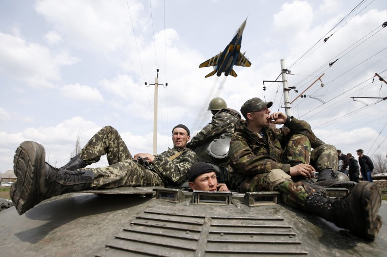 A fighter jet flies above as Ukrainian soldiers sit on an armoured personnel carrier in Kramatorsk, in eastern Ukraine, in this April 16, 2014 file photo. REUTERS/Marko Djurica
