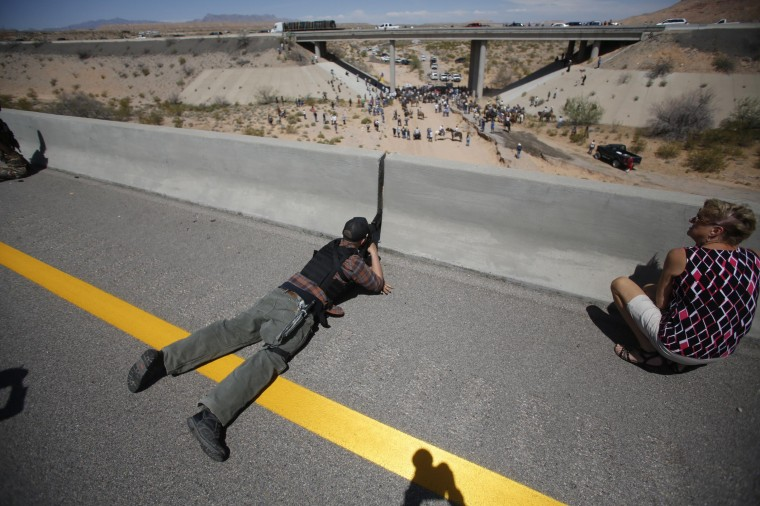Eric Parker from central Idaho aims his weapon from a bridge as protesters gather by the Bureau of Land Management's base camp, where cattle which were seized from rancher Cliven Bundy are being held, near Bunkerville, Nevada, in this April 12, 2014 file photo. REUTERS/Jim Urquhart