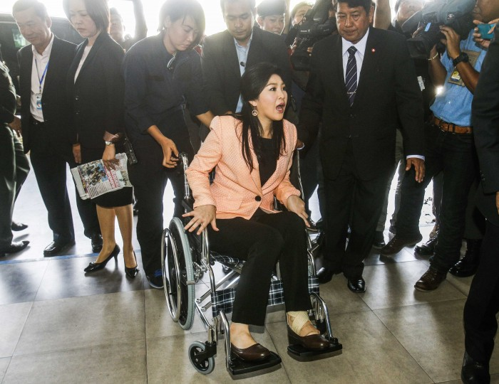 Thailand's Prime Minister Yingluck Shinawatra (C) arrives in a wheelchair at the Royal Police Cadet Academy in Nakorn Pathom province, in this March 18, 2014 file photo. REUTERS/Athit Perawongmetha/Files