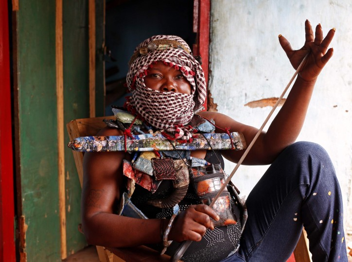 A masked female member of the anti-balaka, a Christian militia, holds a machete as she sits in a village of Zawa, in this April 8, 2014 file photo. REUTERS/Goran Tomasevic