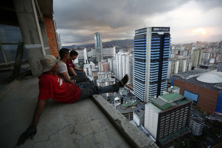 """Men rest after salvaging metal on the 30th floor of the """"Tower of David"""" skyscraper in Caracas, in this February 3, 2014 file photo. REUTERS/Jorge Silva"""