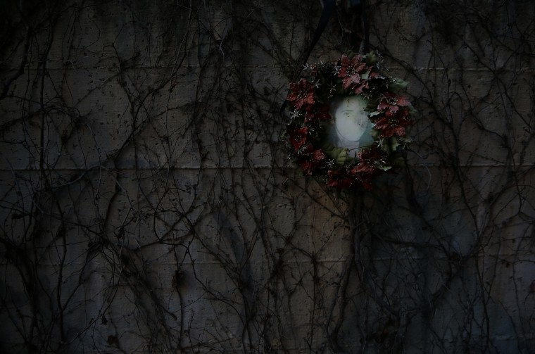 The picture of a young woman is seen at a memorial site for the victims of the March 11 train bombings at the same spot where a train was bombed ten years ago outside Madrid's Atocha station, in this March 11, 2014 file photo. REUTERS/Susana Vera