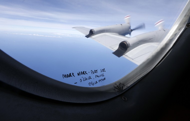 Handwritten notes on how a crew member should report the sighting of debris in the southern Indian Ocean are pictured on a window aboard a Royal New Zealand Air Force P-3K2 Orion aircraft searching for missing Malaysian Airlines flight MH370, in this March 22, 2014 file photo. REUTERS/Jason Reed