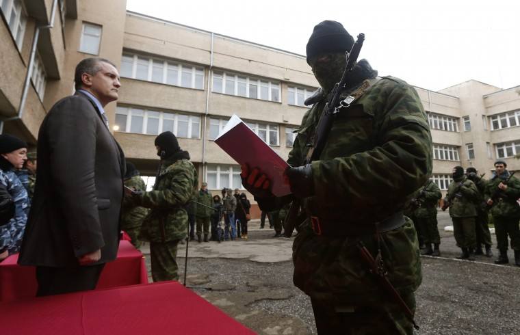 Sergei Aksyonov, Crimea's pro-Russian prime minister, stands as a member of a pro-Russian self defence unit swears an oath to the Crimean government in Simferopol, in this March 10, 2014 file photo. REUTERS/Vasily Fedosenko/Files