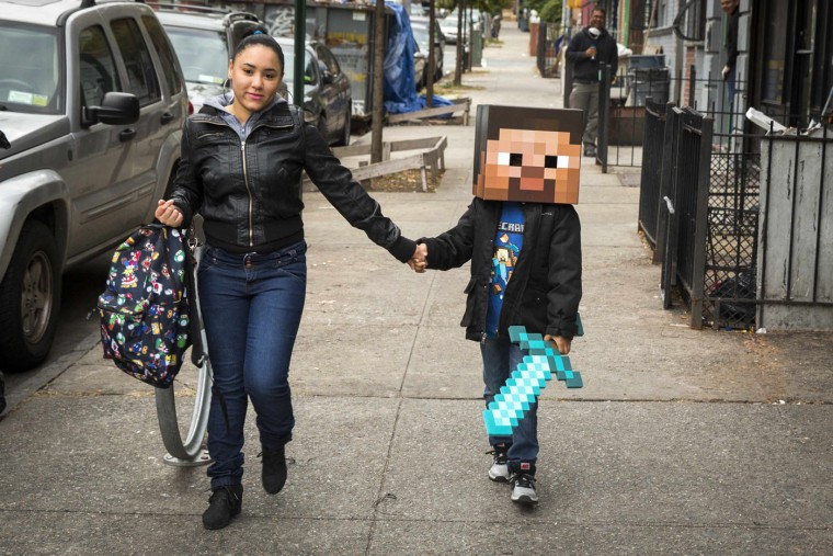 A woman walks her child to school as he is dressed as a character from Minecraft in New York in this October 31, 2014 file photo. REUTERS/Lucas Jackson/Files