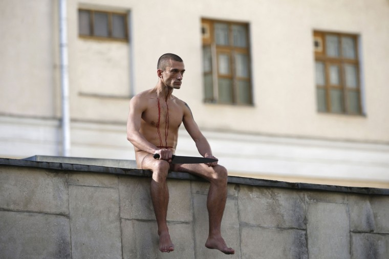 "Artist Pyotr Pavlensky sits on the wall enclosing the Serbsky State Scientific Center for Social and Forensic Psychiatry after he cut off a part of his earlobe during his protest action titled ""Segregation"" in Moscow in this October 19, 2014 file photo. REUTERS/Maxim Zmeyev/Files"