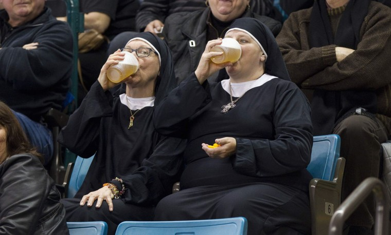Two women wearing nun outfits drink beer while watching the playoff draw between Quebec and Manitoba at the 2014 Tim Hortons Brier curling championships in Kamloops, British Columbia in this March 8, 2014 file photo. REUTERS/Ben Nelms/Files