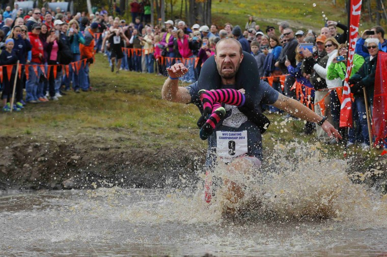 Eventual winners Jesse Wall carries Christina Arsenault through the water pit while competing in the North American Wife Carrying Championship at Sunday River ski resort in Newry, Maine in this October 11, 2014 file photo. REUTERS/Brian Snyder/Files