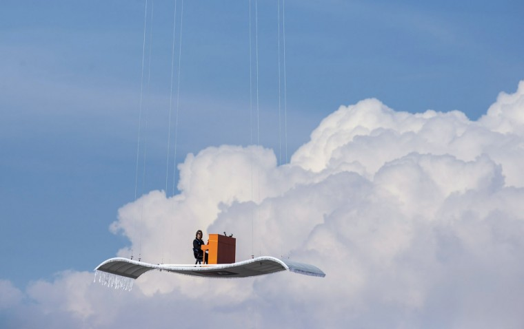 "German pianist Stefan Aaron plays an orange piano on a ""flying carpet"" platform suspended from a helicopter, over the Munich airport in this July 23, 2014 file photo. REUTERS/Lukas Barth/Files"