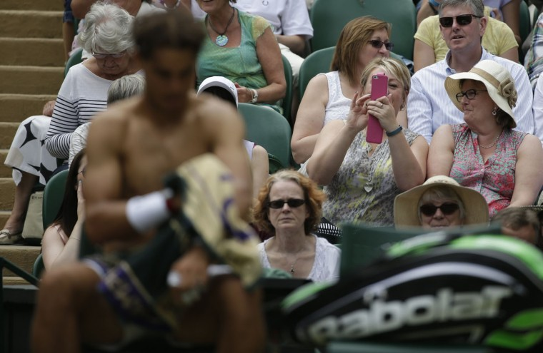 Spectators take photographs of Rafael Nadal of Spain as he changes his shirt during his men's singles tennis match against Lukas Rosol of the Czech Republic at the Wimbledon Tennis Championships, in London, in this June 26, 2014 file photo. REUTERS/Max Rossi/Files
