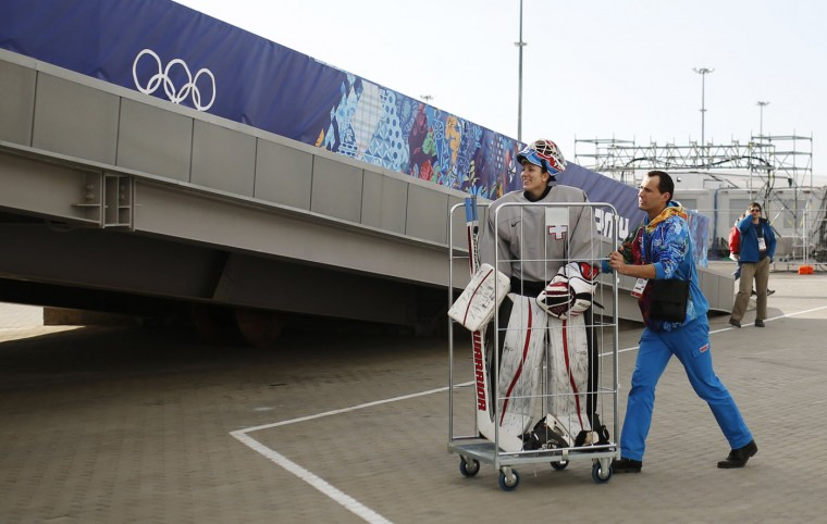 A volunteer pushes Switzerland's goaltender Sophie Anthamatten in a trolley as she leaves the Shayba Arena following a practice session ahead of the 2014 Sochi Winter Olympics, in this February 6, 2014 file photo. REUTERS/Phil Noble/Files