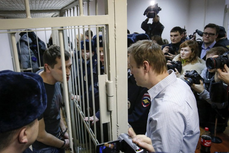 Russian opposition leader and anti-corruption blogger Alexei Navalny (R) talks with his brother and co-defendant Oleg (inside defendants cage) during a court hearing in Moscow December 30, 2014. A Russian court ruled on Tuesday to give Kremlin critic Alexei Navalny a suspended sentence for embezzling money but jailed his brother for three and a half years in a case seen as part of a campaign to stifle dissent. (Sergei Karpukhin/Reuters)