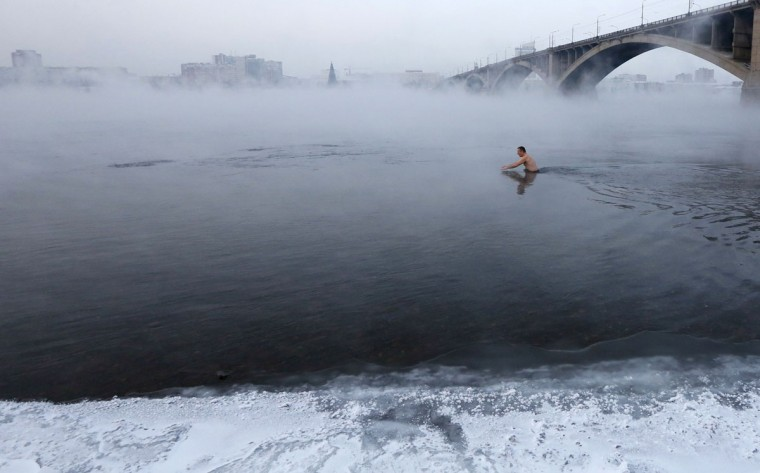 Vladimir Shcherba, 53, a fan of winter swimming, dips to the Yenisei River at air temperature some minus 23 degrees Celsius (-9 Fahrenheit), in Russia's Siberian city of Krasnoyarsk, December 30, 2014. (Ilya Naymushin/Reuters)