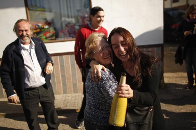 "(L-R) Winners of Spain's Christmas Lottery ""El Gordo"" celebrate in El Gastor, near Cadiz, December 22, 2014. The total prize money of 2.4 billion euros is split into thousands of cash prizes amongst hundreds of winning numbers. (Jon Nazca/Reuters)"