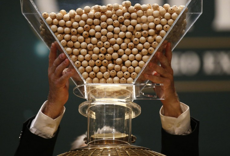 """A man puts the balls into the lottery drum before the draw for Spain's Christmas Lottery """"El Gordo"""" in Madrid December 22, 2014. (Juan Medina/Reuters)"""