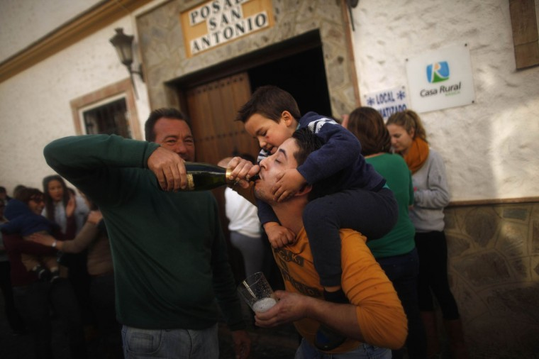 "Winners of Spain's Christmas Lottery ""El Gordo"" celebrate in El Gastor, near Cadiz, December 22, 2014. The total prize money of 2.4 billion euros is split into thousands of cash prizes amongst hundreds of winning numbers. (Jon Nazca/Reuters)"