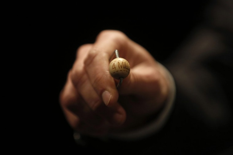 """A man shows a ball before the draw for Spain's Christmas Lottery """"El Gordo"""" in Madrid December 22, 2014. (Juan Medina/Reuters)"""