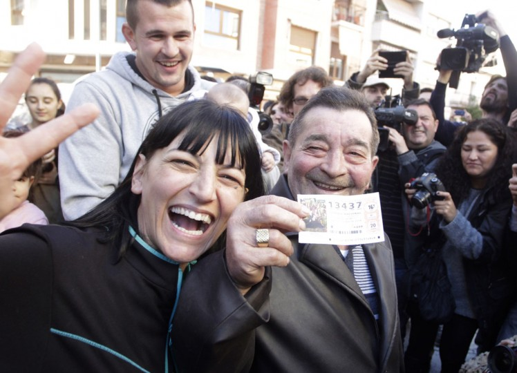 """Juan Lopez holds his lottery ticket with the winning number of Spain's Christmas Lottery """"El Gordo"""", together with his daughter Pilar in La Eliana near Valencia December 22, 2014. The total prize money of 2.4 billion euros is split into thousands of cash prizes amongst hundreds of winning numbers. (Heino Kalis/Reuters)"""