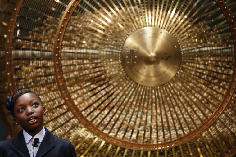 """A schoolgirl stands next to a lottery drum during the draw for Spain's Christmas Lottery """"El Gordo"""" in Madrid December 22, 2014. (Juan Medina/Reuters)"""