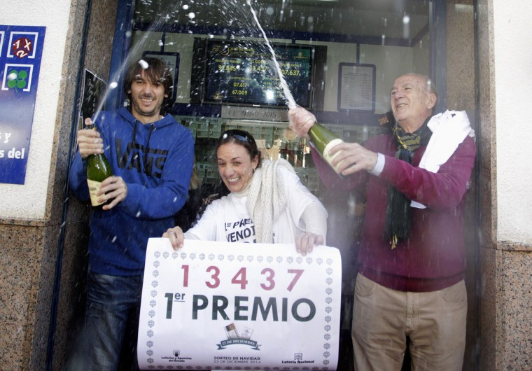 """Lottery seller Raquel Carrasco (C) holds a sign with the winning number of Spain's Christmas Lottery """"El Gordo"""", as employees spray champagne in La Eliana near Valencia December 22, 2014. The total prize money of 2.4 billion euros is split into thousands of cash prizes amongst hundreds of winning numbers.(Heino Kalis/Reuters)"""