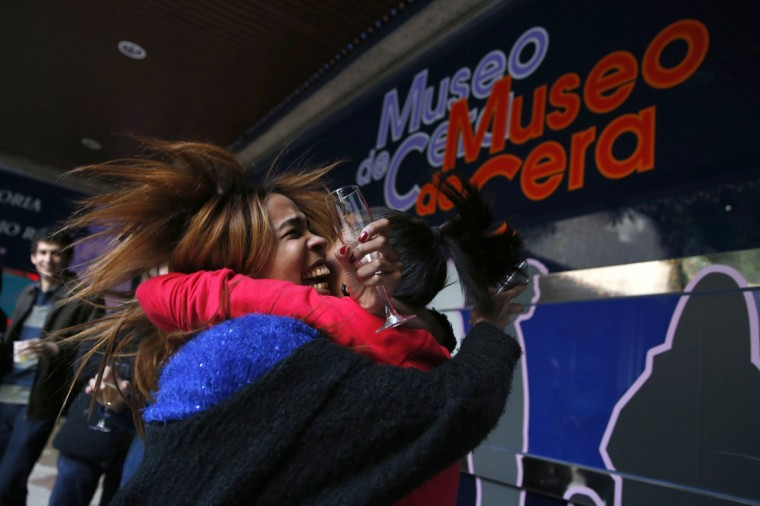 """Madrid Wax Museum employee Noemi Vazquez (L) and her sister Maria celebrate winning a portion of Spain's Christmas Lottery """"El Gordo"""" in Madrid December 22, 2014. The total prize money of 2.4 billion euros is split into thousands of cash prizes amongst hundreds of winning numbers. (Juan Medina/Reuters)"""