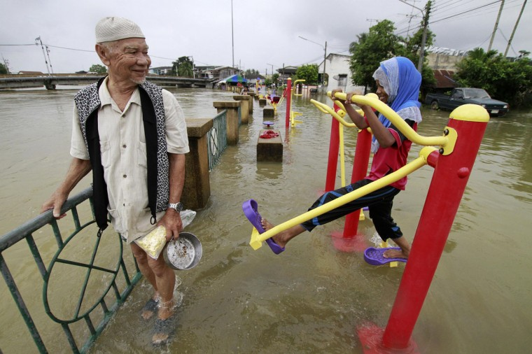 A man wades through a flooded street as a girl uses an exercise machine in the Pattani province December 29, 2014. Many parts of Thailand's southern provinces remain flooded and more heavy rains and strong winds were expected until the New Year, local media reported. (Surapan Boonthanom/Reuters)