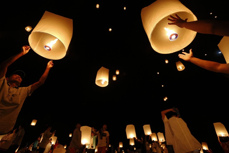 Survivors, local residents and visitors release paper lanterns during a ceremony for victims of 2004 tsunami in Ban Nam Khem, a southern fishing village destroyed by the wave December 26, 2014. Survivors of Asia's 2004 tsunami and relatives of its 226,000 victims gather along shorelines of the Indian Ocean on Friday for prayers and memorial services to mark the 10th anniversary of a disaster that still leaves an indelible mark on the region. In Thailand, where 5,395 people were killed, among them about 2,000 foreign tourists, commemoration ceremonies will be held in Ban Nam Khem. REUTERS/Athit Perawongmetha