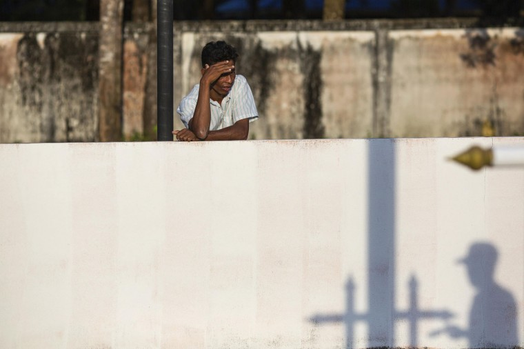 A man looks into the Tsunami Victims Cemetery as a worker painting flag poles casts a shadow outside Ban Nam Khem, in Phang Nga province, December 12, 2014.