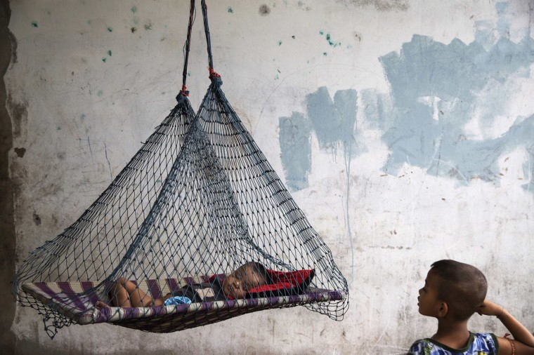 A son of a migrant fisherman from Myanmar rests in a hammock at a former shrimp warehouse where his family lives in Ban Nam Khem, December 13, 2014. Ban Nam Khem, a small fishing village on Thailand's Andaman Sea coast and home to a large migrant workers' community, lost nearly half of its 5,000 population in the tsunami.