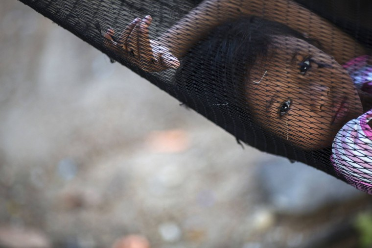 Soe, the eight-year-old daughter of a fisherman from Myanmar, rests in a hammock outside her family home in Ban Nam Khem December 13, 2014. Ban Nam Khem, a small fishing village on Thailand's Andaman Sea coast and home to a large migrant workers' community, lost nearly half of its 5,000 population in the tsunami.