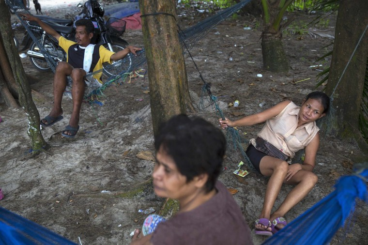 Local people rest in hammocks in Ban Nam Khem, December 13, 2014. Ban Nam Khem, a small fishing village on Thailand's Andaman Sea coast and home to a large migrant workers' community, lost nearly half of its 5,000 population in the tsunami.