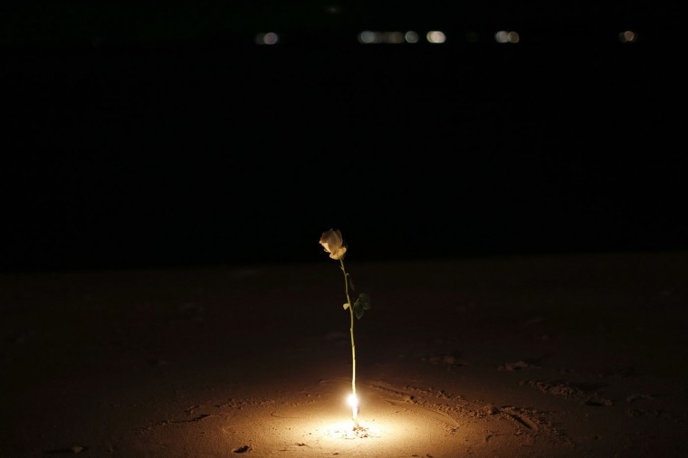 A rose is lit by a candle as survivors, local residents and visitors gather for a ceremony for victims of the 2004 tsunami in Ban Nam Khem, a fishing village destroyed by the wave December 26, 2014. Survivors of Asia's 2004 tsunami and relatives of its 226,000 victims cried and prayed as they gathered along Indian Ocean shorelines on Friday for memorials to mark the 10th anniversary of a disaster that still leaves an indelible mark on the region. REUTERS/Athit Perawongmetha