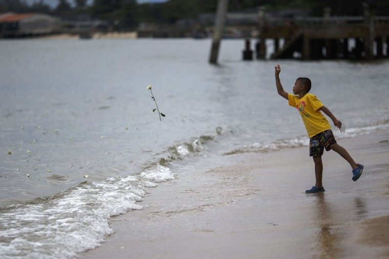A boy throws a rose into the sea near a monument for victims of the 2004 tsunami in Ban Nam Khem, a southern fishing village destroyed by the tsunami, December 26, 2014. Survivors of Asia's 2004 tsunami and relatives of its 226,000 victims cried and prayed as they gathered along Indian Ocean shorelines on Friday for memorials to mark the 10th anniversary of a disaster that still leaves an indelible mark on the region. REUTERS/Athit Perawongmetha